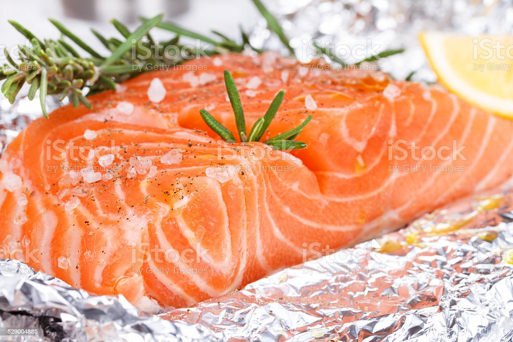 Fresh salmon ready for cooking on the foil paper stock photo