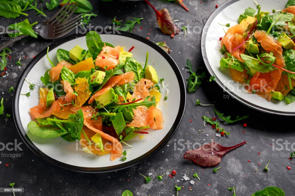 Fresh salmon salad with avocado, orange and green vegetables stock photo