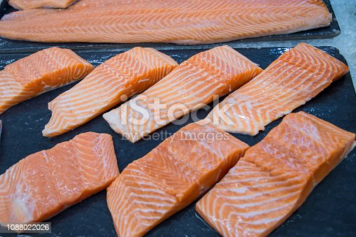 Fresh salmon. Salmon fillets for sale at a fish market displayed with a patchwork effect. Many fresh salmon fish meat slices in a black tray which are sale in the supermarket or department store.
