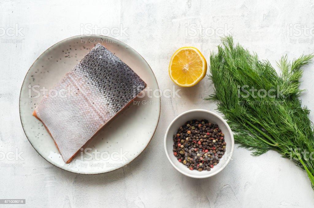 Fresh salmon steak, lemon, pepper and dill on concrete table. stock photo