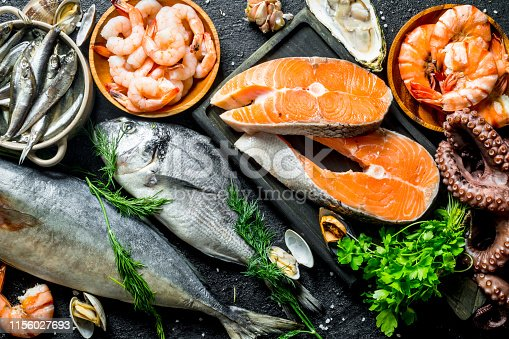 Fresh salmon steak with a variety of seafood and herbs. On black rustic background