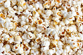 White and yellow fresh salted popcorn texture background. Close up top view food pattern photography
