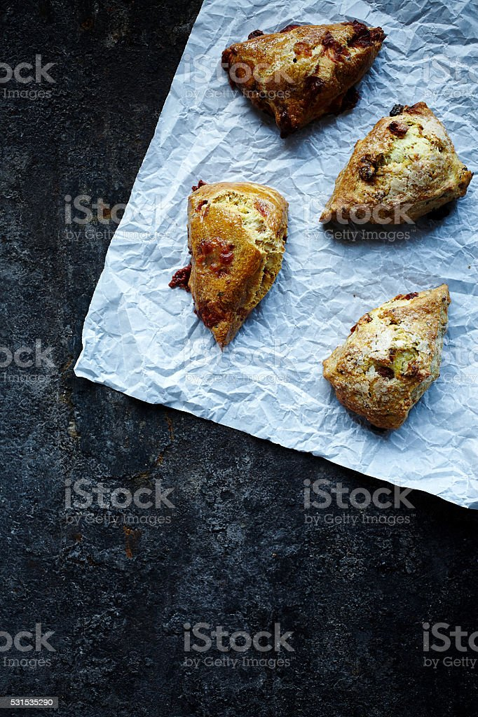 Fresh salty scones on baking paper stock photo