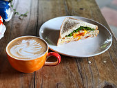 Fresh sandwich and swan shape Latte art coffee cup on the wooden table. Delicious Breakfast , Natural Light and copy space