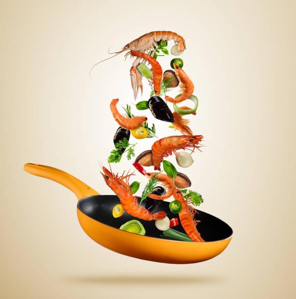 frische meeresfrüchte und gemüse in einer pfanne auf braunem hintergrund fliegen - chefkoch auflauf stock-fotos und bilder