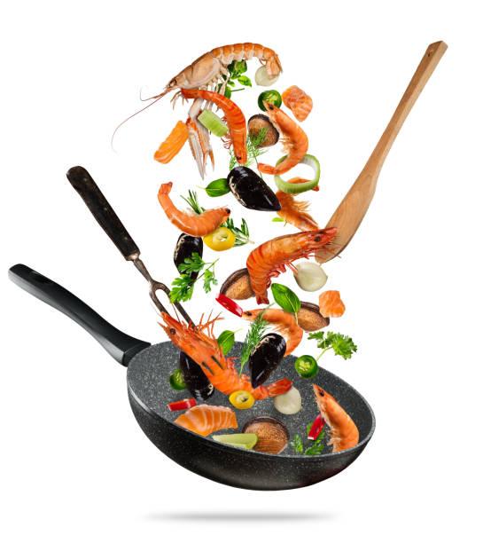 frische meeresfrüchte und gemüse in einer pfanne auf weißem hintergrund fliegen - chefkoch auflauf stock-fotos und bilder