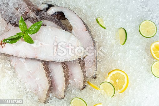fresh sea ocean white fish sliced in pieces, lying on ice, headless, cherry, sliced lemon and lime sliced round, lay around, with green basil, light, side view from above