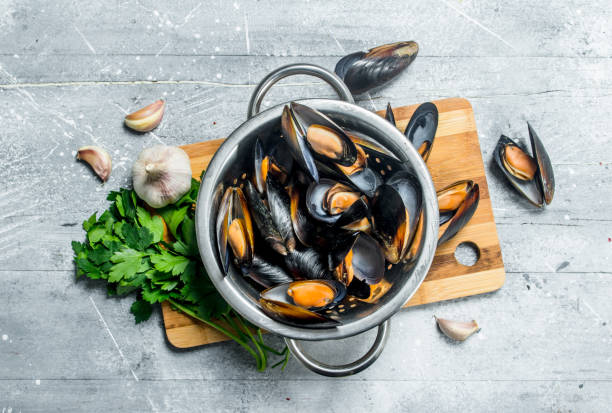 Fresh seafood clams with parsley and garlic. Fresh seafood clams with parsley and garlic. On a rustic background. mussel stock pictures, royalty-free photos & images