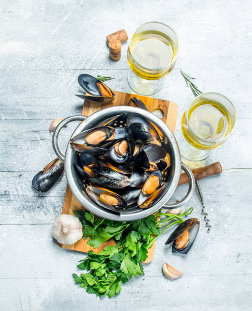 Fresh seafood clams with parsley and white wine. Fresh seafood clams with parsley and white wine. On a rustic background. mussel stock pictures, royalty-free photos & images