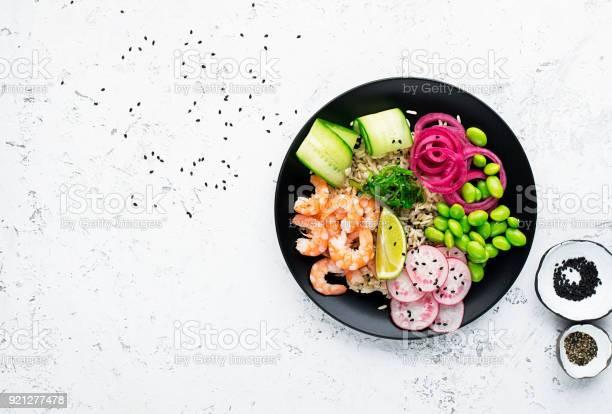 新鮮な魚介類のレシピ海老は新鮮なエビ玄米キュウリ甘いオニオンのピクルス大根大豆豆枝豆黒と白胡麻の部分のフードでボールを突きますフードボウル概念突くトップ ビュー - アブラナ科のストックフォトや画像を多数ご用意