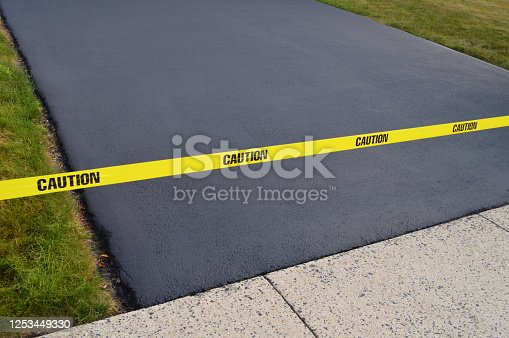 Finished result of paved seal coated blacktop driveway with caution tape.