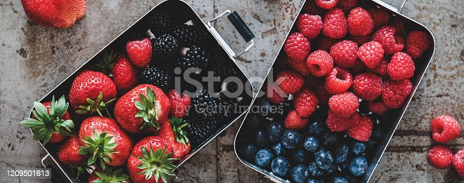 Healthy summer vegan lunch. Flat-lay of fresh seasonal strawberries, raspberries, blueberries and blackberries in lunchboxes over grey background, top view, wide composition. Vegetarian, detox food