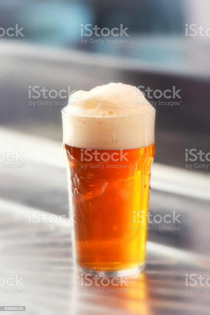 Fresh served pint of frothy draft beer in a glass stock photo