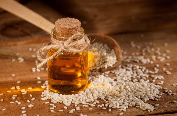 Fresh sesame oil in a glass bottle and seeds in a wooden spoon stock photo