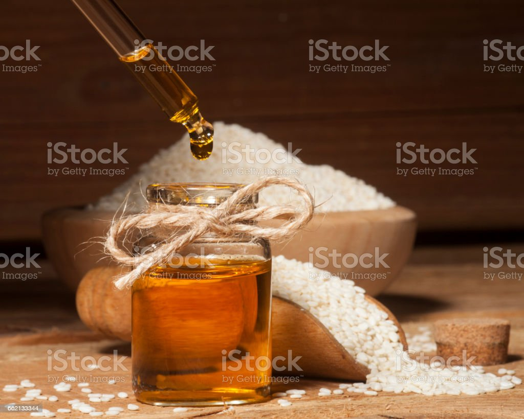 Fresh sesame oil in a glass bottle and seeds in wooden bowl and spoon stock photo