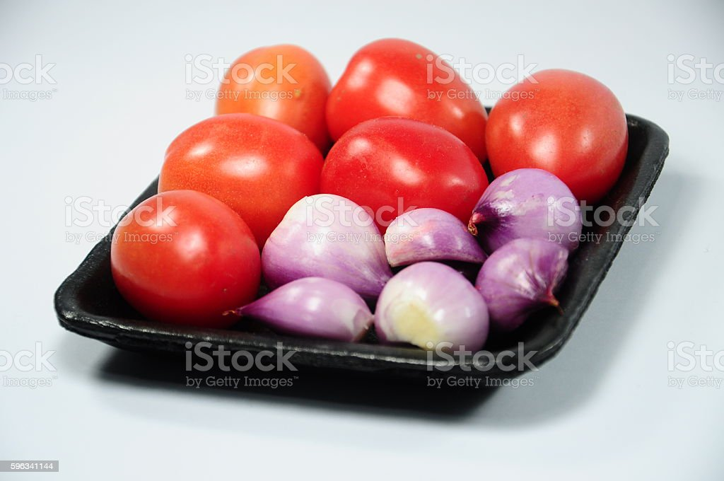 Fresh shallots and red tomatoes on black tray Lizenzfreies stock-foto