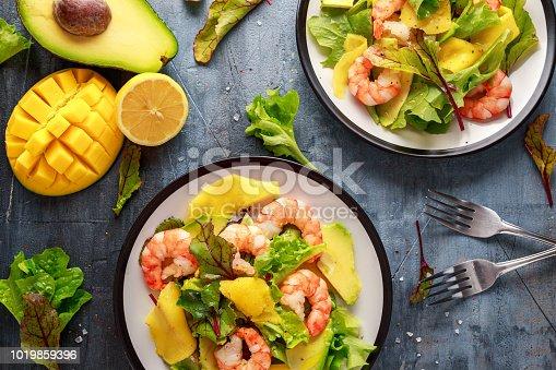 Fresh Shrimps, Avocado, Mango salad with lettuce green mix, herbs, lemon, healthy food
