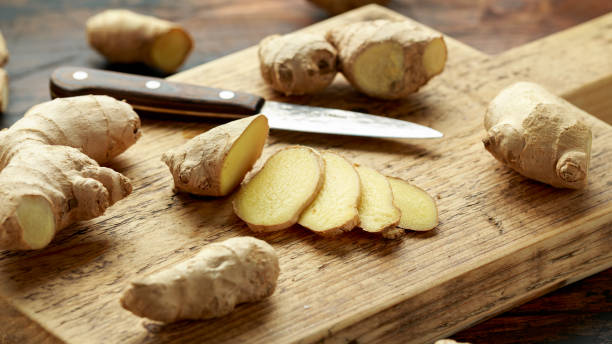 Fresh slice of Ginger on wooden chopping board. healthy food stock photo