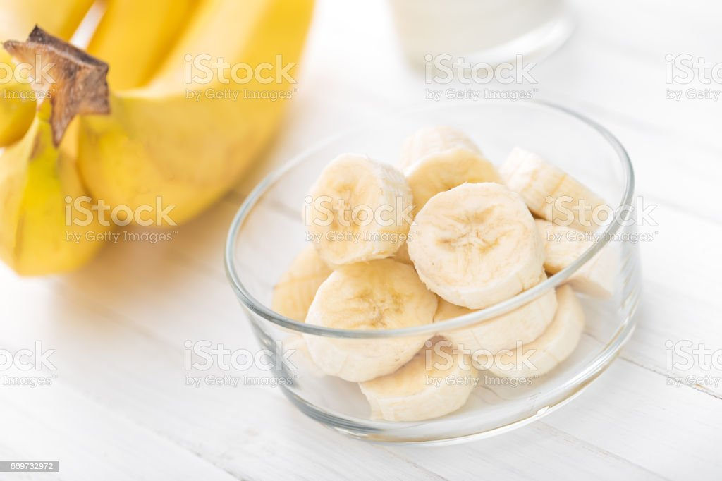 Fresh sliced bananas on white wooden background closeup, healthy eating stock photo