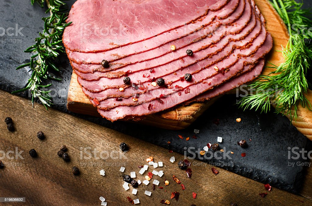 fresh sliced beef pastrami surrounded by herbs, wooden chopping board stock photo