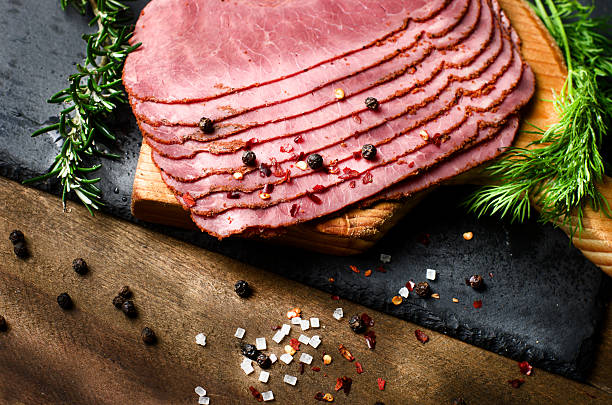 fresh sliced beef pastrami surrounded by herbs, wooden chopping board - pastrami stock pictures, royalty-free photos & images