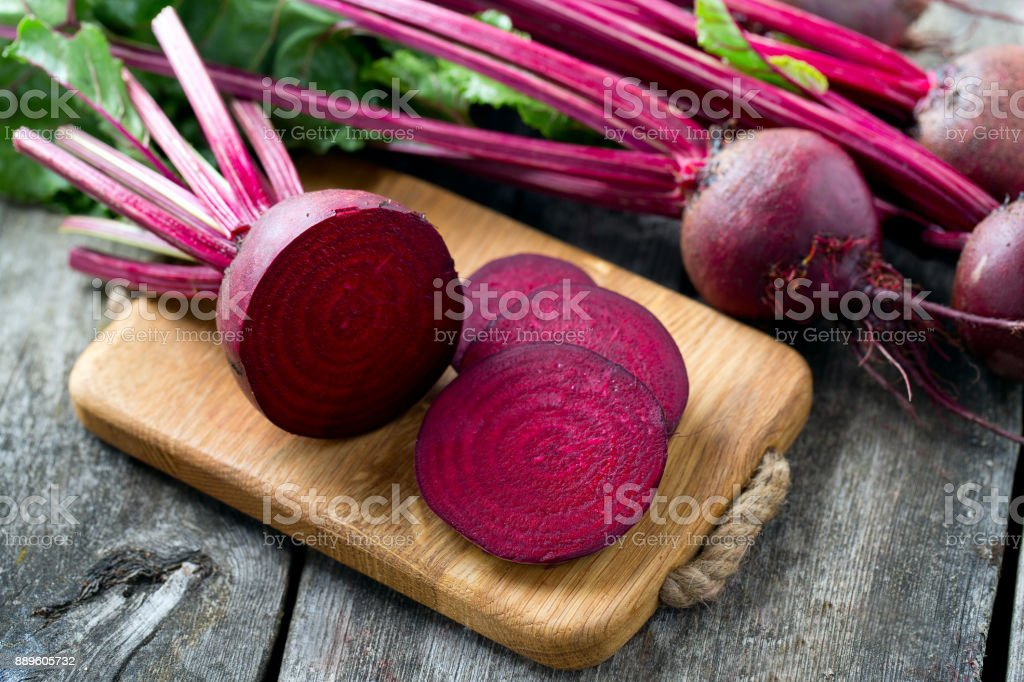 fresh sliced beetroot on wooden surface stock photo
