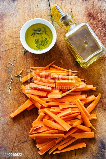 Carrot sticks, cut on a cutboard with a small bowl with  olive oil, ready to be prepared as typical italian