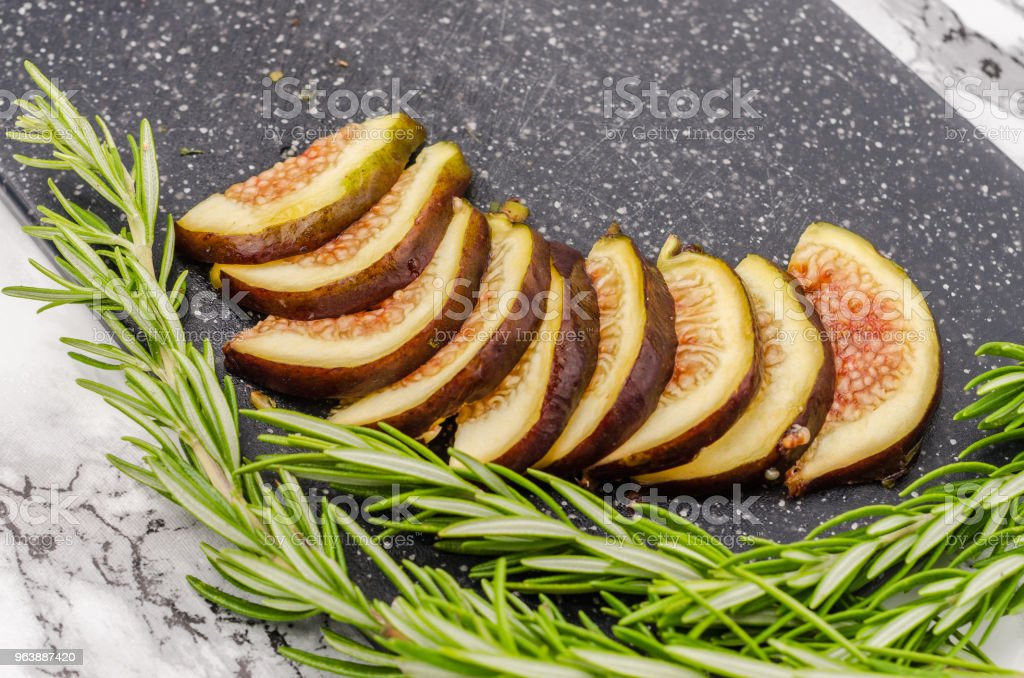 Fresh sliced figs and rosemary on cutting board - Royalty-free Appetizer Stock Photo