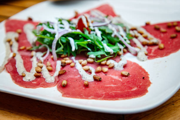 Fresh Sliced raw beef meat with leaf lettuce on the table stock photo
