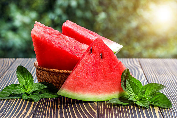 fresh sliced watermelon wooden background - karpuz stok fotoğraflar ve resimler