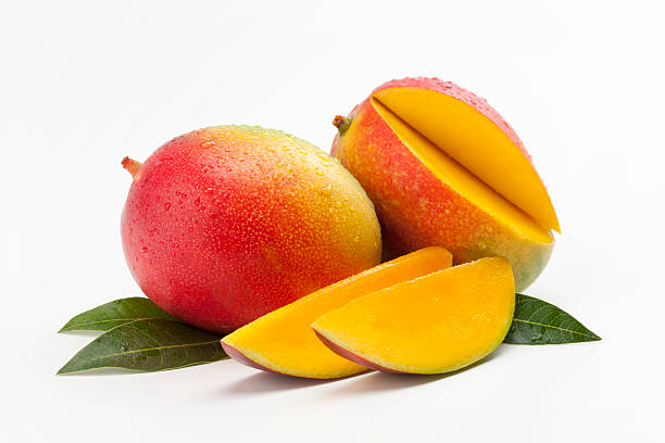 Fresh Slices of Mango on a Bed of Leaves Mango. mango stock pictures, royalty-free photos & images