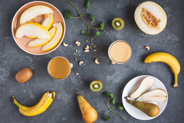 frischer smoothie mit kiwi, banane, birne und melone. flach zu legen - melonenbirne stock-fotos und bilder