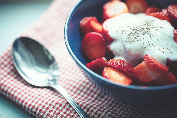 fresh snipped strawberries in the bowl with natural yoghurt and chia seeds stock photo
