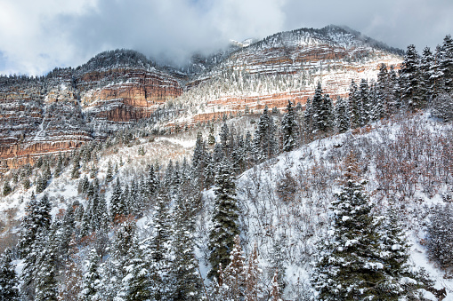 Storm clouds lift to reveal a beautifu, fresh coating of snow in Ouray Colorado.