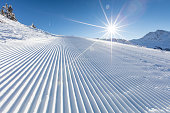 Fresh snow on ski slope during sunny day, Alps mountains.