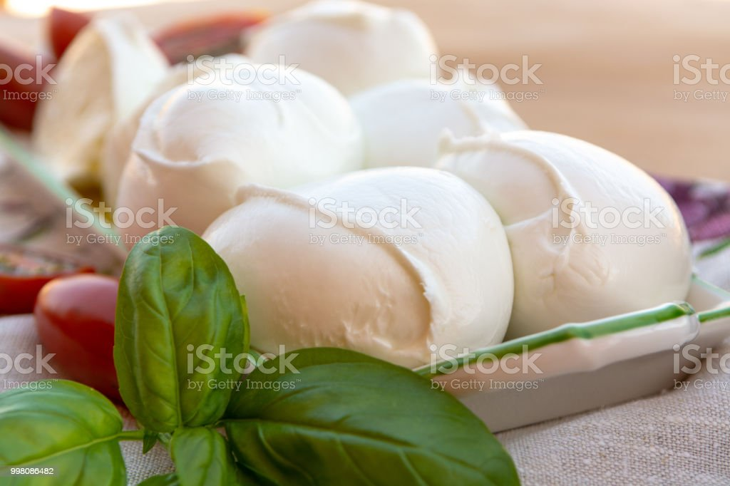 Fresh soft Italian white cheese mozzarella buffalo, original from Campania, Paestrum and Foggia regions, South Italy, served with tomatoes and fresh basil stock photo