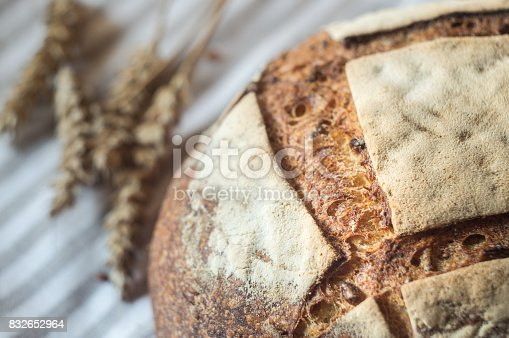 913749618istockphoto Fresh sourdough bread and ears of wheat, close up 832652964