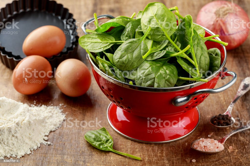 Fresh spinach in red colander with ingredients to cook spinach quiche stock photo