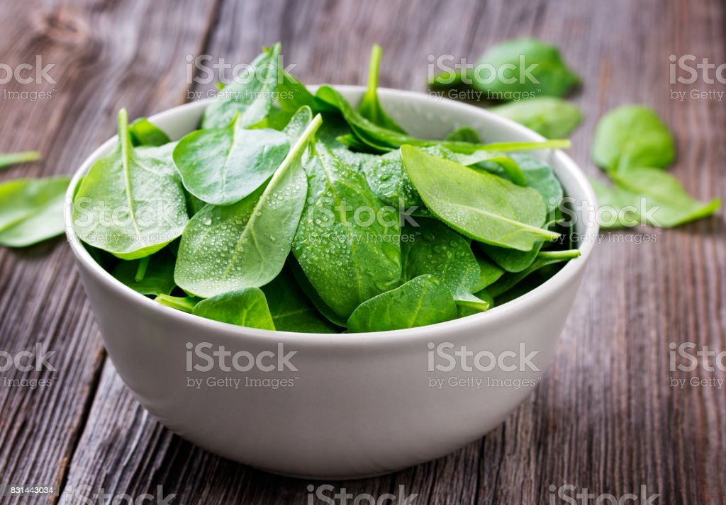 Fresh spinach leafs with drops in a bowl on a rustic wooden table stock photo