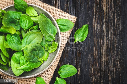 Green spinach leaves in bowl on rustic wooden table. Top View