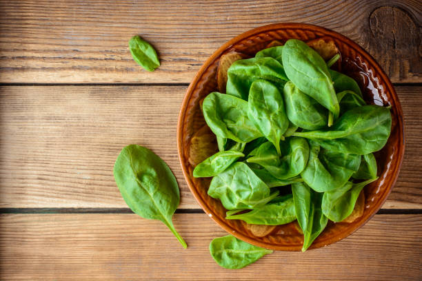 Fresh spinach leaves in bowl on rustic wooden table. stock photo