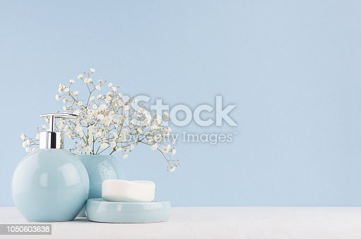 istock Fresh spring decor for bathroom with small white flowers, ceramic vase and soap pump bottle on white wood board. 1050603638