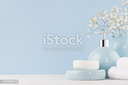 istock Fresh spring decor for bathroom with small white flowers, ceramic vase and soap pump bottle, towel on white wood board. 1070932312