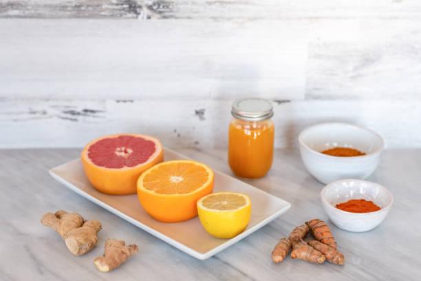 fresh squeezed citrus turmeric juice for wellness - flu shot zdjęcia i obrazy z banku zdjęć