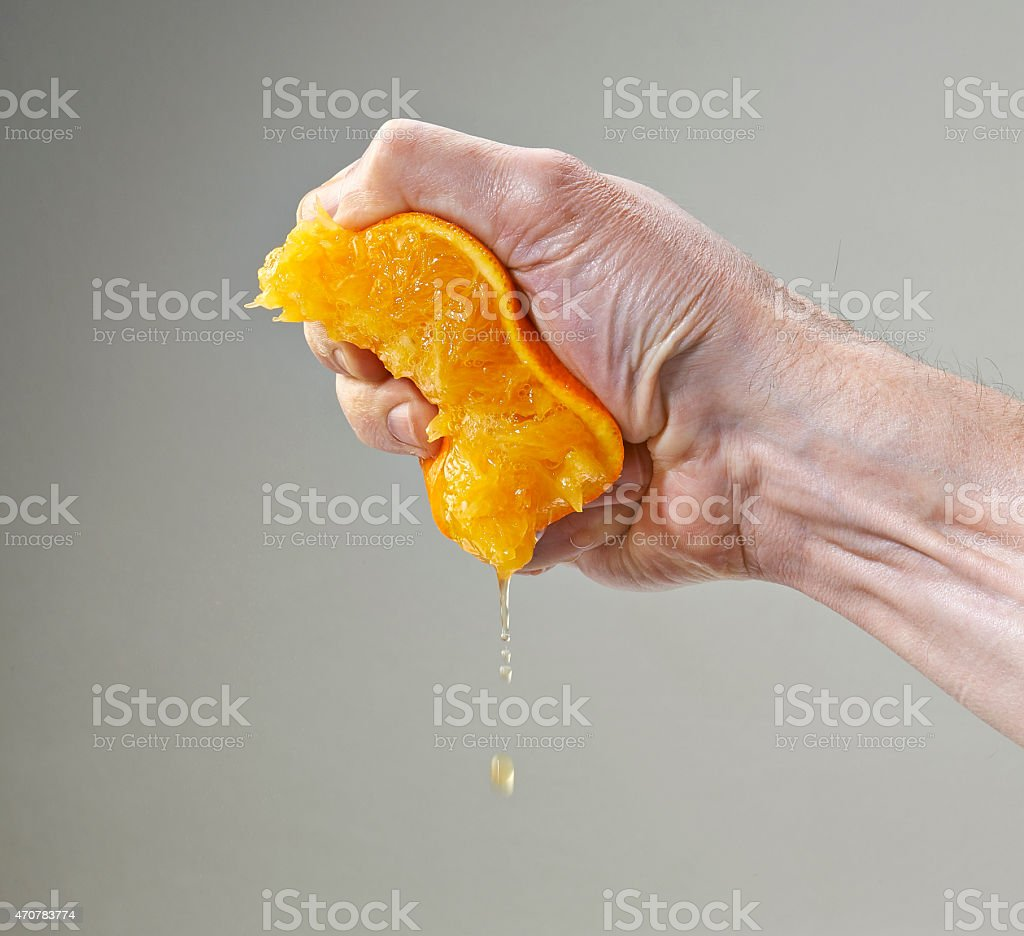Fresh Squeezed Orange Juice by Male Hand stock photo
