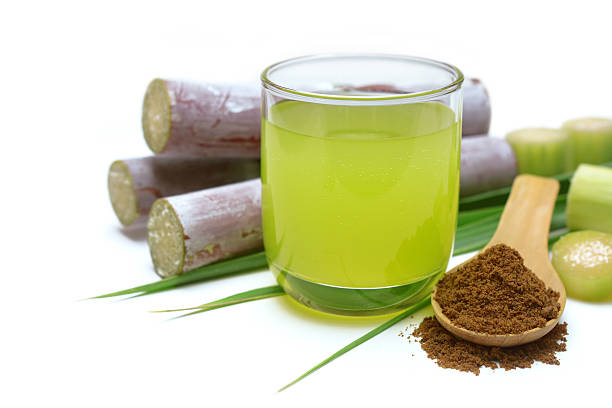 Fresh squeezed sugar cane juice. Fresh squeezed sugar cane juice in clear glass with cut pieces cane and brown sugar on white background. sugar cane stock pictures, royalty-free photos & images