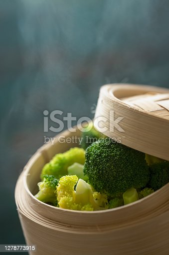 Colorful contrasting freshly steamed bright green healthy organic broccoli spears in a bamboo dim sum steamer with a turquoise colored wood background, good copy space at the top of the image.