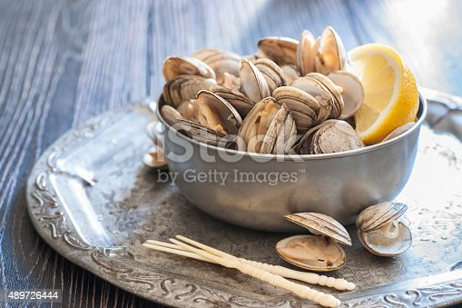 High resolution digital capture of a metal bowl containing freshly steamed clams and a wedge of fresh lemon. The bowl sits on a tin tray which sits on a wooden surface. Two vintage plastic seafood picks are crossed inset at the bottom of the shot.