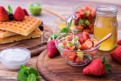 Waffles with fresh strawberries and kiwi with honey and Greek yogurt, close up