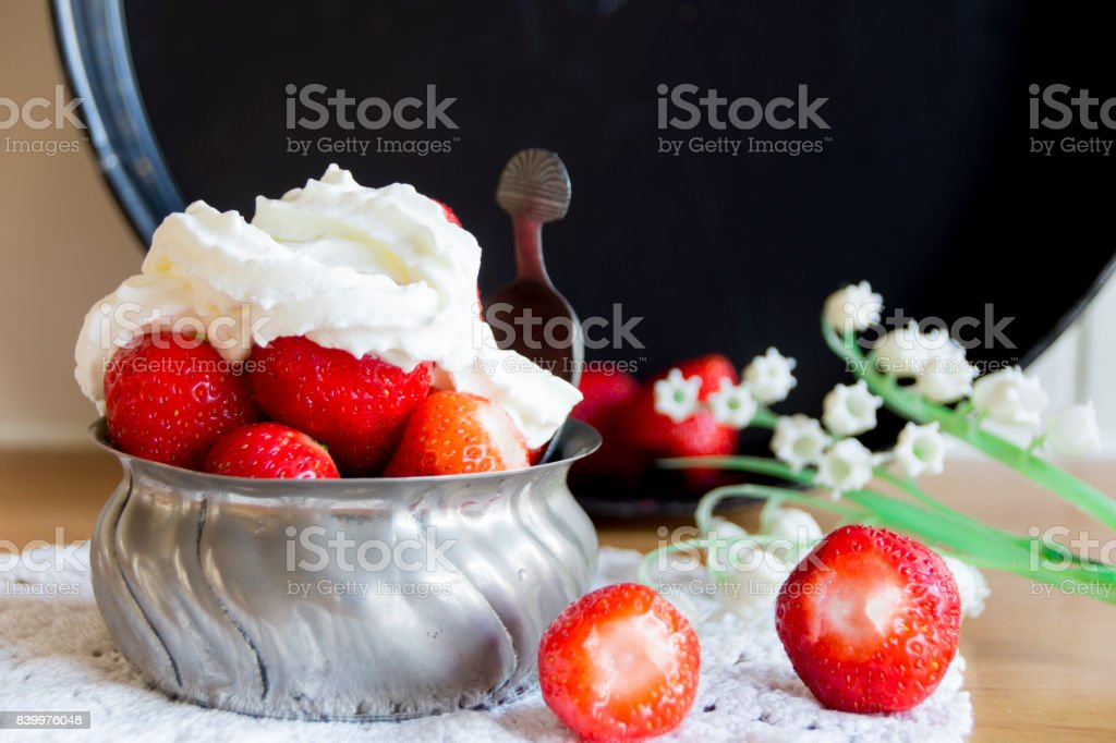 fresh strawberries and whipped cream in metal bowl with spoon and white flower stock photo